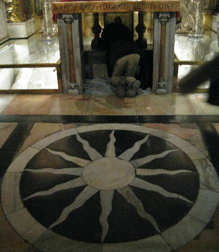 The symbol of the sun on the floor of the Church of the Holy Tomb in Jerusalem near Golgotha ​​(in the background)